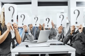 Business people holding question mark signs.