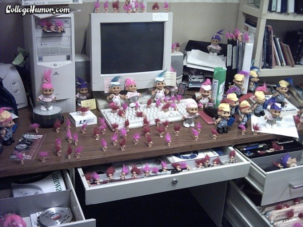 Office desk full of pink troll dolls