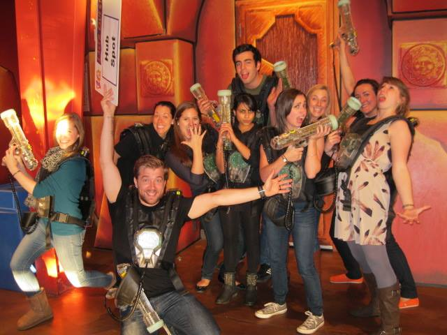 Group of coworkers playing laser tag as a teamwork game
