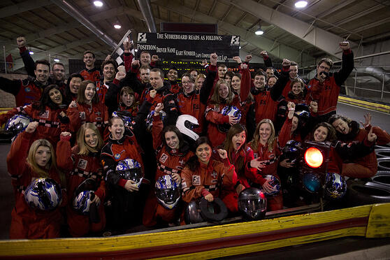 Small group of coworkers going go-kart racing in red uniforms