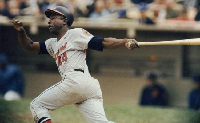 professional baseball player Hank Aaron of the Atlanta Braves swinging a baseball bat in a baseball stadium