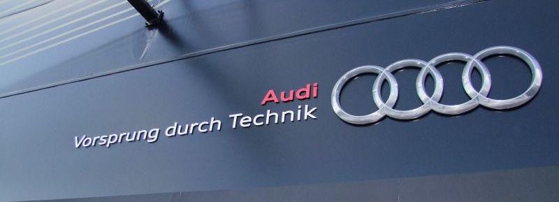 Audi's tagline, says Vorsprung durch technik, written on a black storefront