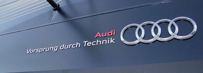 Audi's tagline, says Vorsprung durch technik, written on a black storefront