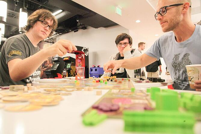 Three male coworkers playing in a board game tournament