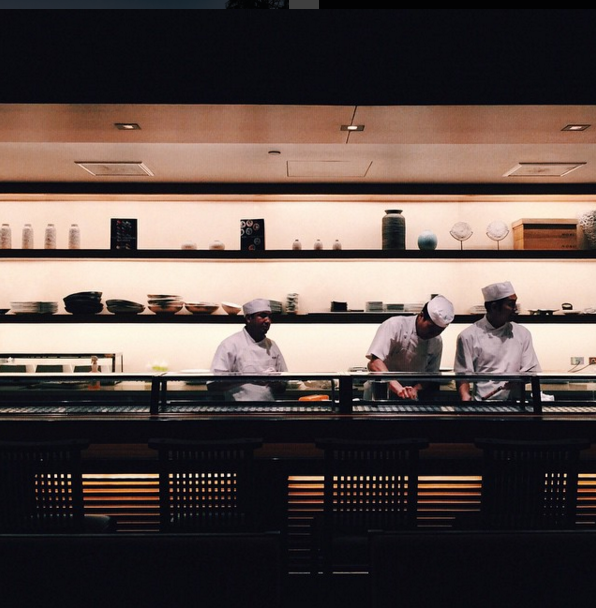Candid shot of three chefs cooking, taken with phone camera