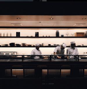 Toma sincera de tres cocineros cocinando, tomada con la cámara del teléfono