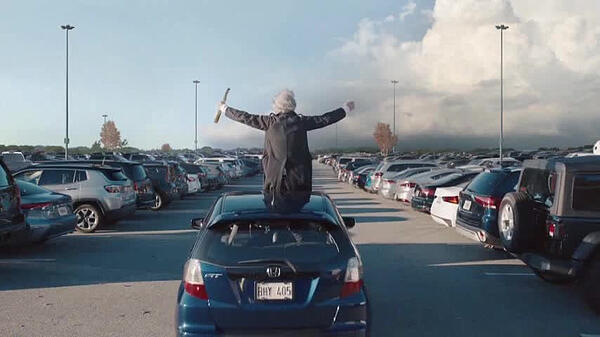 Geico TV ad with a person riding on top of car in a parking lot