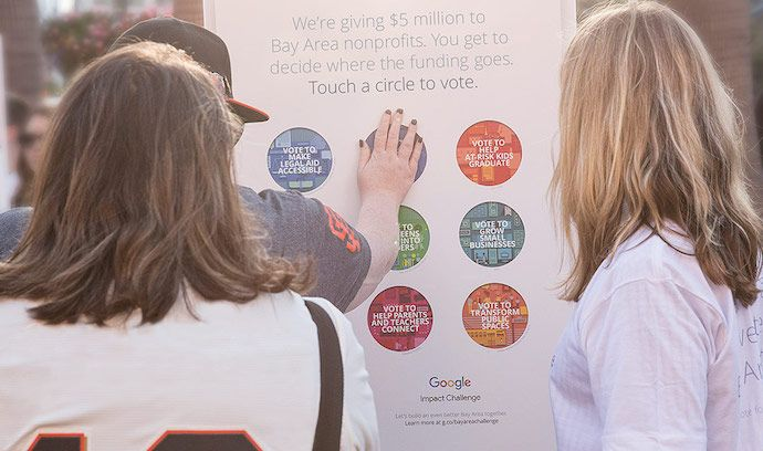 Women touching an interactive poster by Google, as part of the company's experiential marketing campaign, Building a Better Bay Area
