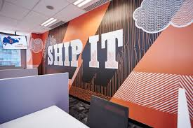 Orange mural that says 'ship it' on a wall at HubSpot's Singapore office