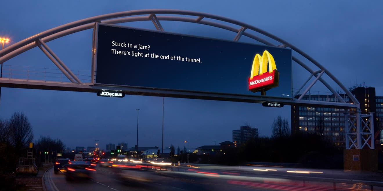 "mcdonalds billboard that reads ""stuck in a jam? There's light at the end of the tunnel"" next to golden arches sign"