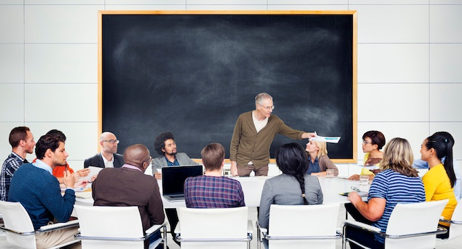Coworkers sitting around a lecturer hosting a professional development workshop