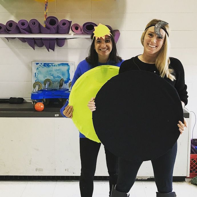 Two girls dressed in solar eclipse costume at an office
