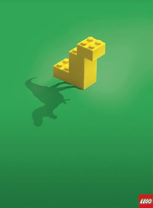 a lego ad that displays a t-rex in the shadow of a blocky lego shape