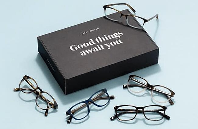 Warby parker glasses strewn across box that reads Good Things Await You