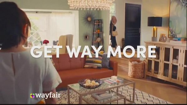 """Wayfair TV programmatic ad on TV. A woman stands in a furnished room with the overlaid text: """"GET WAY MORE"""""""