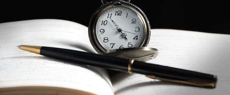 A pocket watch and pen on an open blank journal
