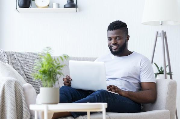 man using a laptop to install a Google AdSense alternative on his blog website