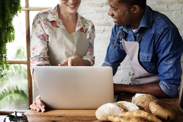 two bakers using a laptop to create a bakery website