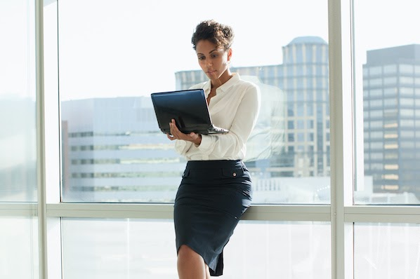 woman standing holding a laptop and renewing an SSL certificate for her website