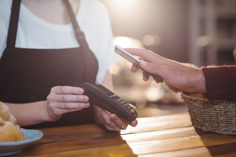 Customer paying bill through smartphone using NFC technology in cafe.jpeg