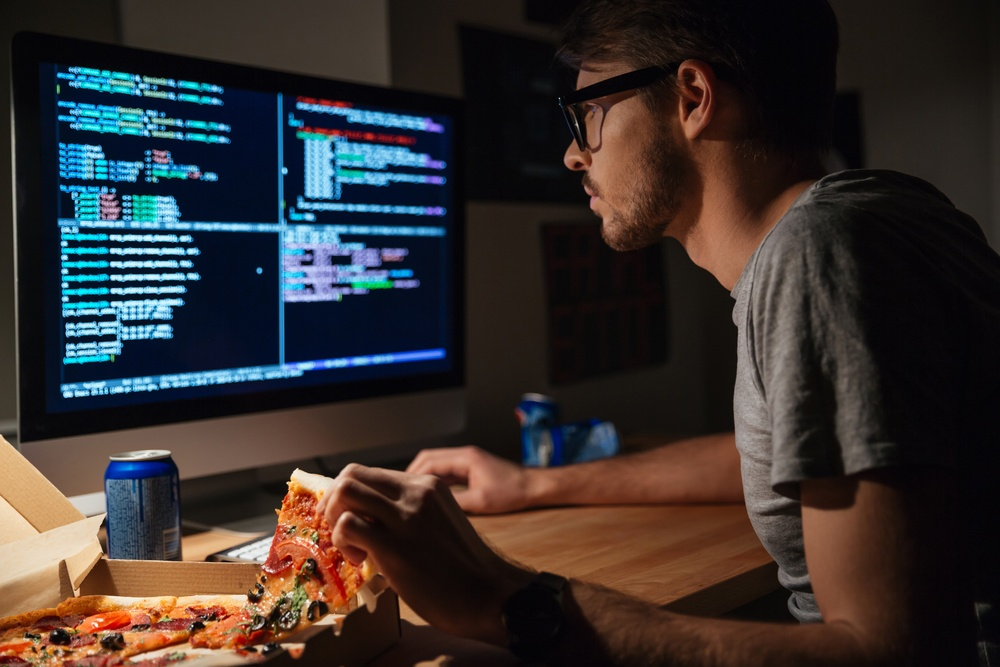Profile of concentrated young software developer eating pizza and coding at home.jpeg
