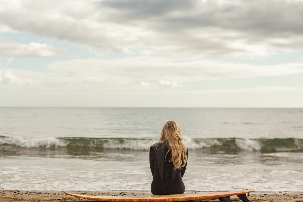 Rear view of a young blond in wet suit with surfboard at the beach.jpeg