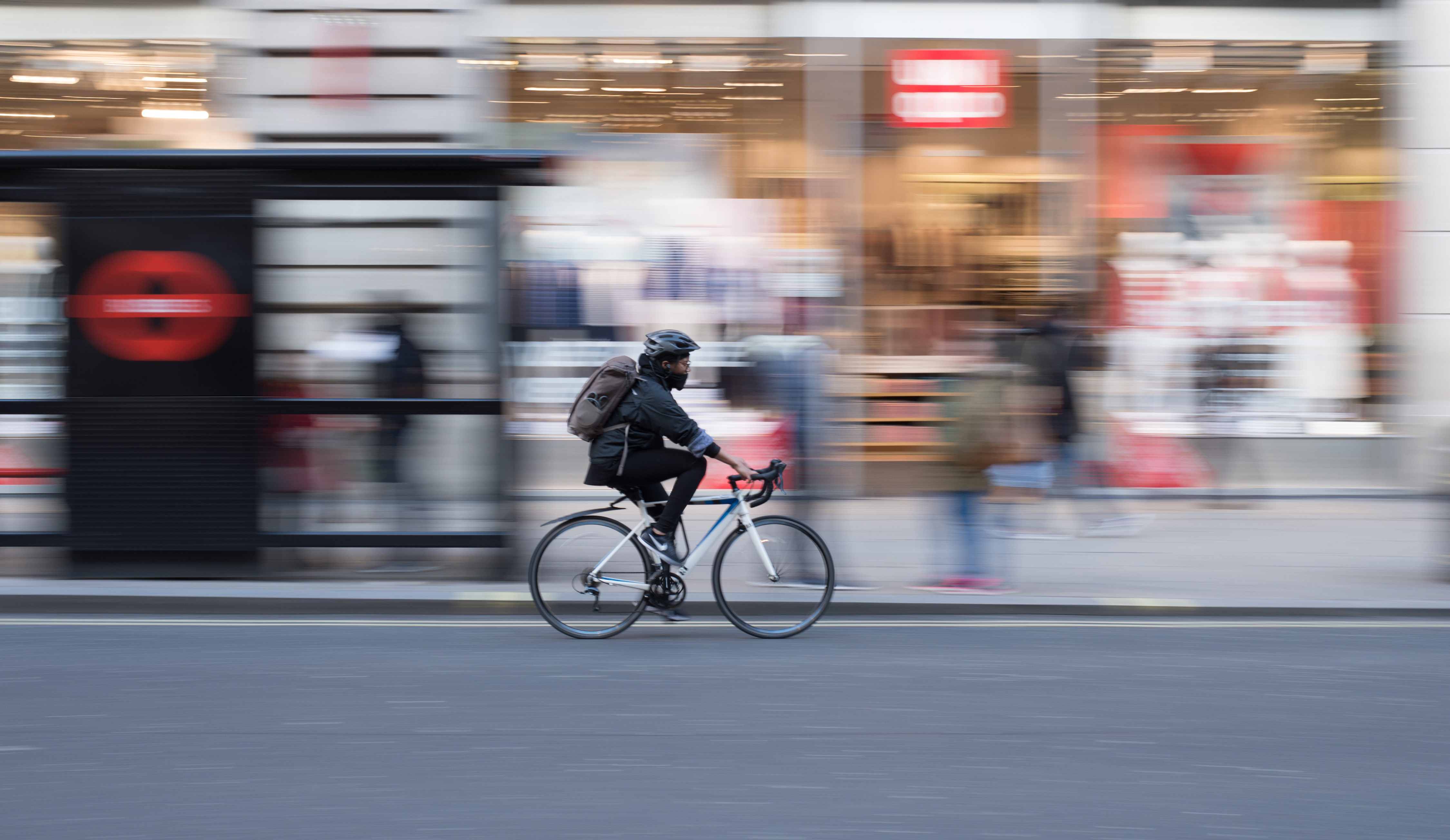 In-focus cyclist riding in front of blurred shop windows.