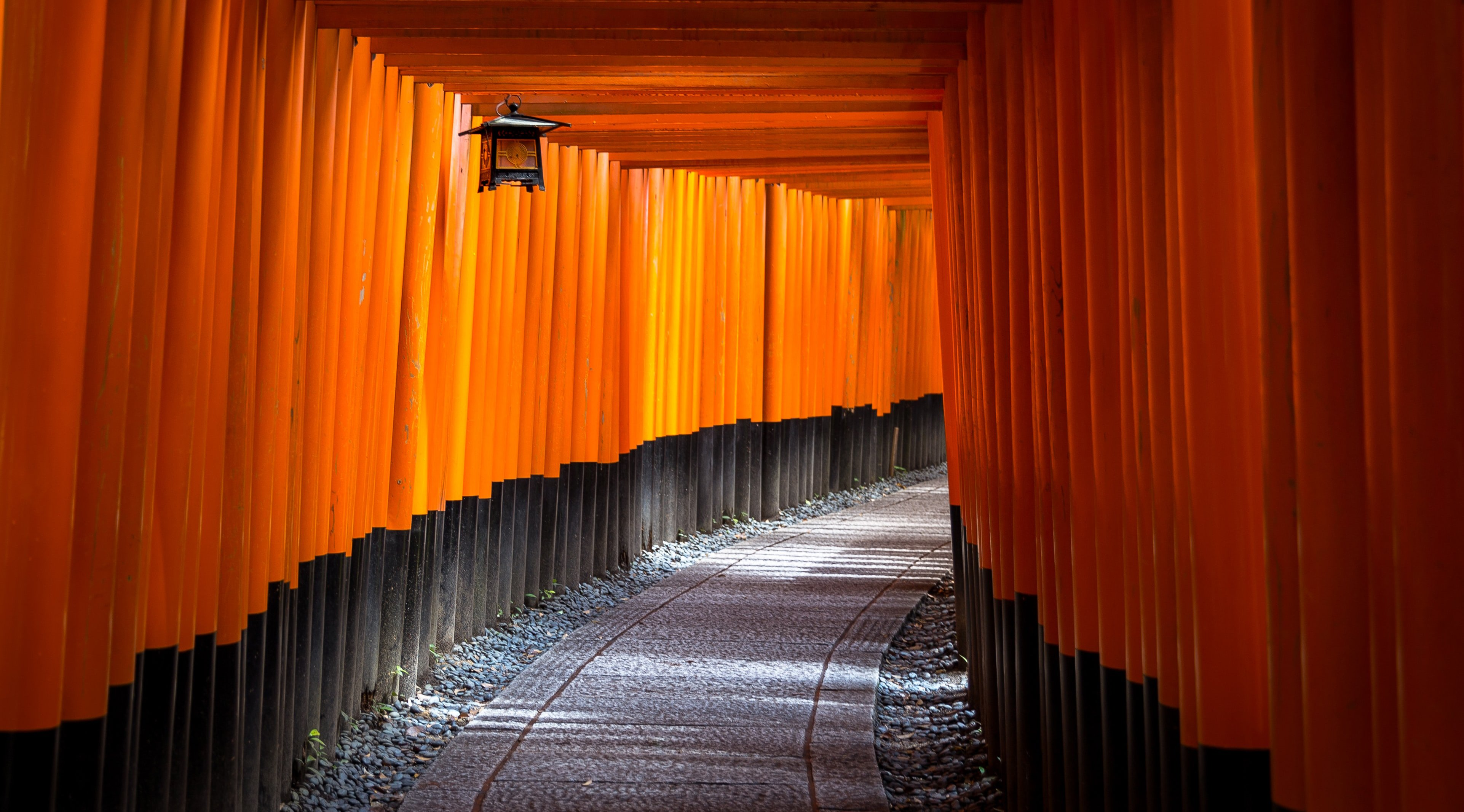 Sequence of orange, square arches, lined up one after another with a hanging lantern.