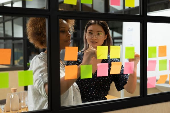 Two women use sticky notes to boost productivity at work.