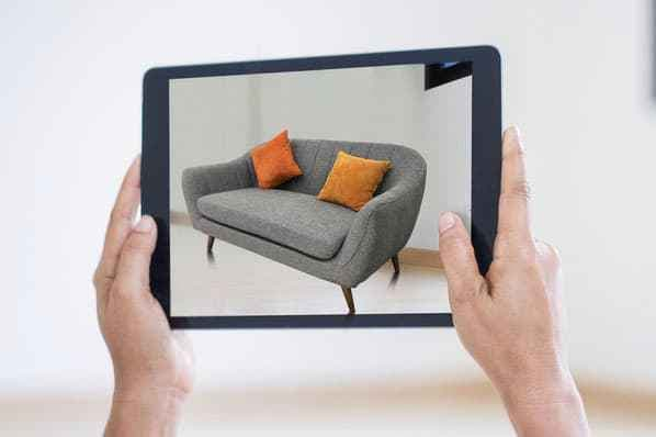A person previews a couch with an AR product preview.
