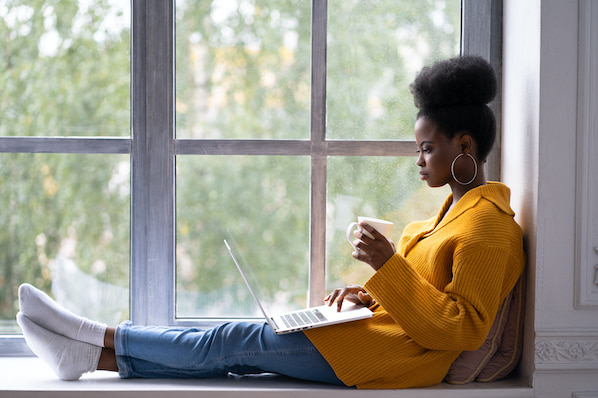 woman sitting in a windowsill using a laptop to use a tool for finding long-tail keywords