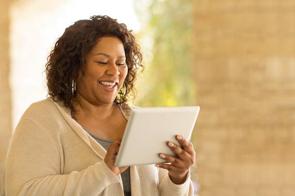 woman using a tablet to browse for digital downloads wordpress themes