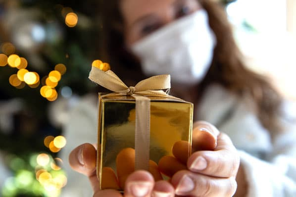 A person gives a gift they bought while holiday shopping online during the COVID-19 pandemic.