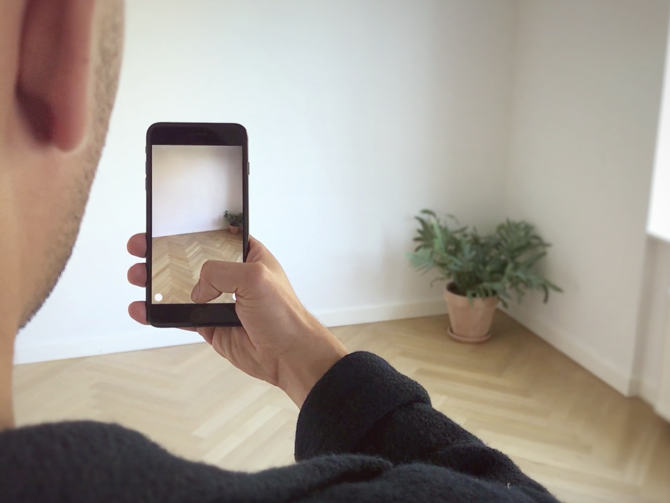 Man holding mobile device up to plant to experience IKEA Place, an AR app to visualize furniture