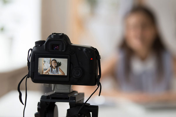 A woman films a marketing video remotely from her own home.