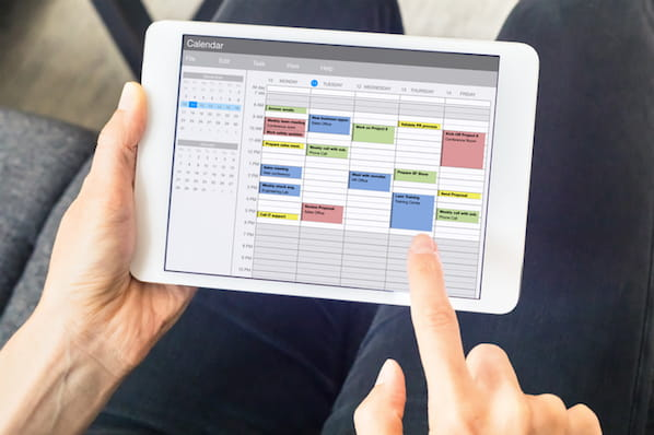 marketer using a social media content calendar tool on a tablet