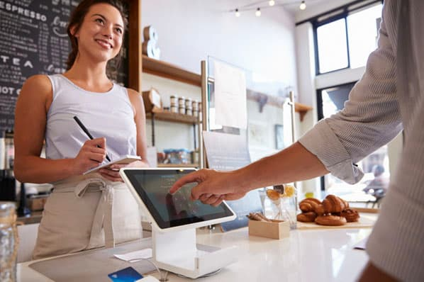 A person pays for food with an ipad at a cafe with the help of Square software