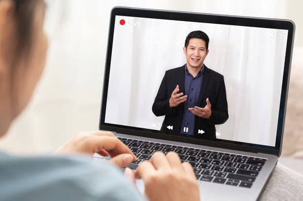 A marketing agency client reviews a recorded virtual marketing campaign pitch from a marketer.