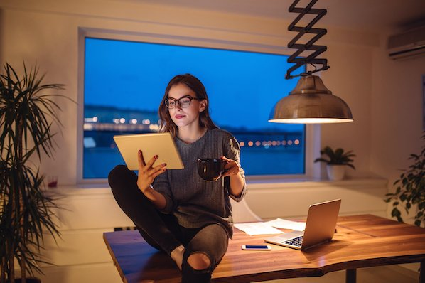 woman using a tablet in her home office to browser for the best job board wordpress themes