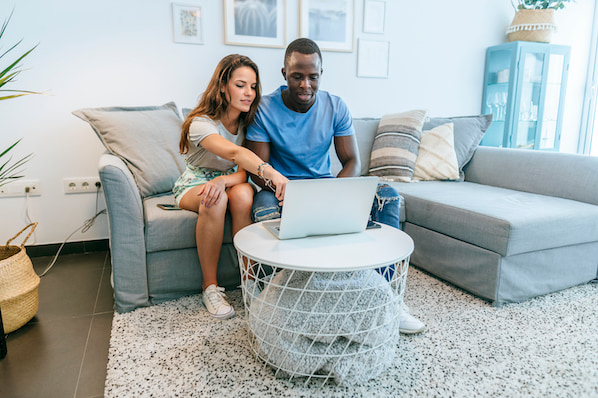 two people sitting on a couch using a laptop to select a wordpress theme framework for their wordpress website