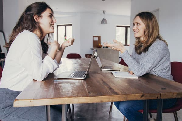 Two professionals navigate while working remotely with roommates or family.